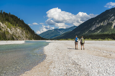 Germany, Bavaria, back view of two hikers with backpacks walking in dry creek bed - DIGF02800