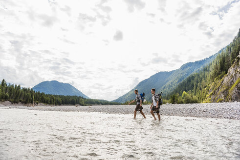 Germany, Bavaria, two hikers with backpacks crossing Isar River - DIGF02803
