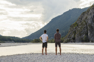 Germany, Bavaria, back view of two friends looking at view at riverside - DIGF02824