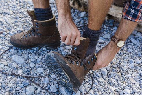 Hiker putting on his shoes, partial view - DIGF02827