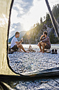 Germany, Bavaria, two hikers camping on gravel bank in the evening - DIGF02830