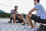 Germany, Bavaria, two hikers having a rest at camp fire on gravel bank - DIGF02836
