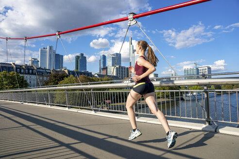 Germany, Frankfurt, young woman running on bridge - PUF00693