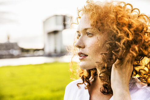 Germany, Cologne, portrait of freckled young woman with curly red hair - FMKF04383