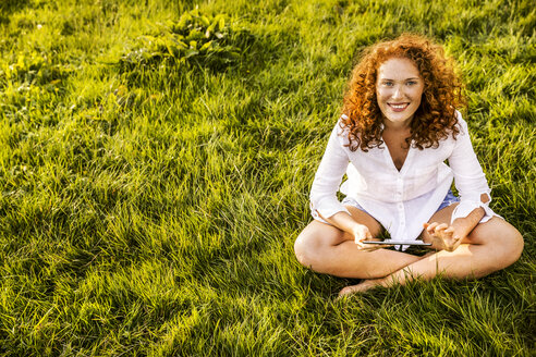 Portrait of happy young woman with tablet relaxing on a meadow - FMKF04386