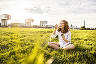 Germany, Cologne, portrait of happy young woman eating jelly on meadow - FMKF04389