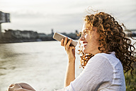 Germany, Cologne, portrait of laughing young woman on the phone sitting at riverside in the evening - FMKF04395