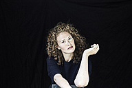 Portrait of young woman with curly  hair in front of black background - FMKF04401