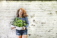 Portrait of young woman with fresh herbs in a box leaning against white brick wall - FMKF04410