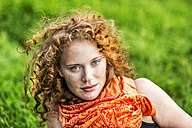 Portrait of freckled young woman with curly red hair wearing orange scarf - FMKF04419