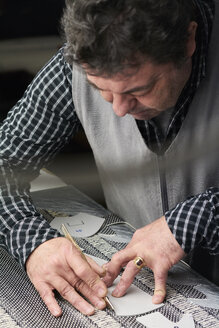 Shoemaker working on template in his workshop - IGGF00140
