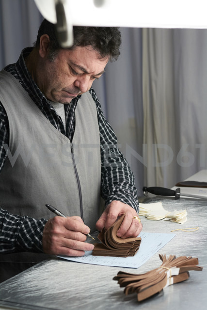 Shoemaker looking at samples in his workshop - IGGF00143
