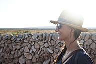 Spain, Menorca, happy single traveller wearing straw hat and sunglasses at backlight - IGGF00146