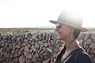 Spain, Menorca, happy single traveller wearing straw hat and sunglasses at backlight - IGGF00146