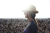 Spain, Menorca, smiling single traveller wearing straw hat at backlight - IGGF00149