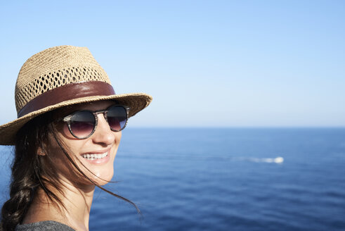Portrait of smiling woman wearing straw hat and sunglasses in front of the sea - IGGF00155