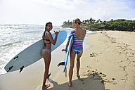 Two women running on the beach with surfboards - ECPF00055