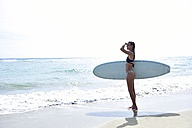 Woman at the ocean with surfboard - ECPF00058