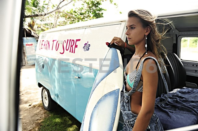 Portrait of woman with surfboard at van - ECPF00073