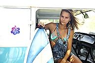 Portrait of woman with surfboard in van - ECPF00076