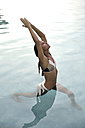 Young woman stretching in swimming pool - ECPF00106