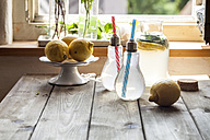 Homemade lemonade with mint on wooden table in front of window - SBDF03298