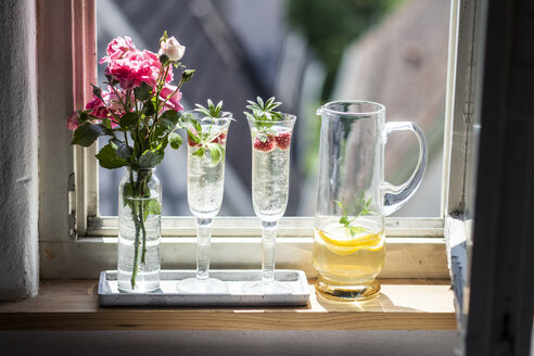 Two Champagne glasses of may wine with raspberries on window sill - SBDF03301
