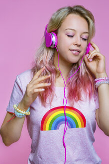 Portrait of young woman listening to music with headphones in front of pink background - MGIF00097