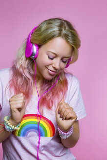 Portrait of dancing young woman listening to music with headphones in front of pink background - MGIF00100