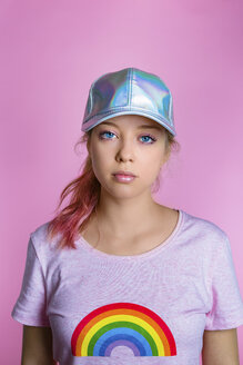 Portrait of stylish young woman wearing basecap in front of pink background - MGIF00106
