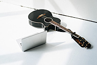 Laptop and acoustic guitar on white floor - JOSF01526