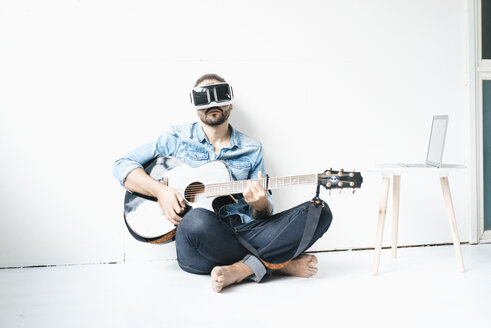 Man with guitar wearing Virtual Reality Glasses sitting on the floor - JOSF01532