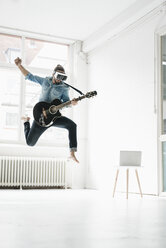 Man with guitar wearing Virtual Reality Glasses jumping in the air in a loft - JOSF01535