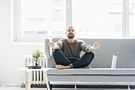 Portrait of man with eyes closed sitting on the couch doing yoga exercise - JOSF01544