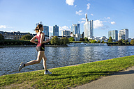 Germany, Frankfurt, young woman running at riverside - PUF00698