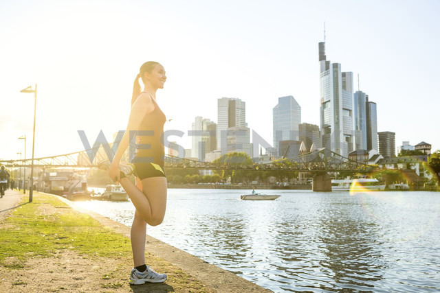 Germany, Frankfurt, young woman stretching at riverside - PUF00701