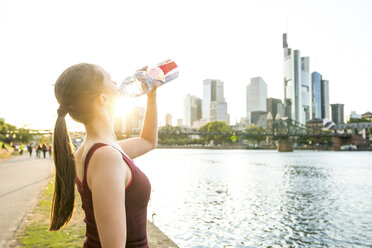 Germany, Frankfurt, sportive young woman drinking from bottle at riverside - PUF00704