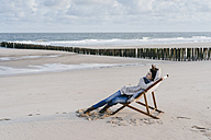 Woman sitting on deckchair on the beach - KNSF02541