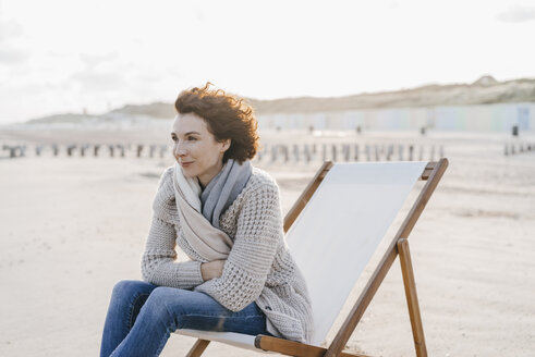 Woman sitting on deckchair on the beach - KNSF02547
