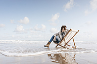 Woman sitting on deckchair on the beach - KNSF02550
