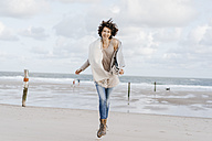 Happy woman running on the beach - KNSF02556