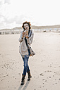 Woman walking on the beach with cell phone and headphones - KNSF02559