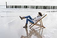 Woman sitting on deckchair on the beach - KNSF02571