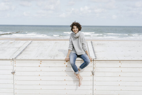 Smiling woman sitting on wooden box on the beach - KNSF02583
