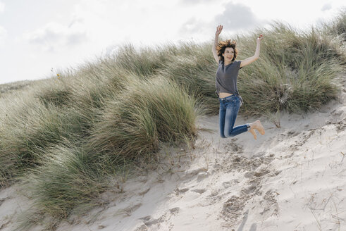 Happy woman jumping in beach dune - KNSF02589