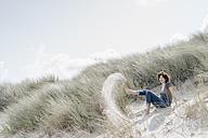 Playful woman sitting in beach dune - KNSF02592