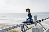 Portrait of smiling woman sitting on railing at the beach - KNSF02598