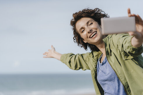 Happy woman on vacation taking a selfie - KNSF02604