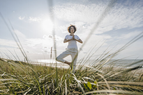 Woman practicing yoga in beach dune - KNSF02607