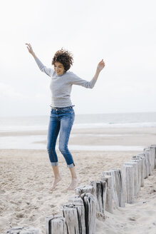 Happy woman jumping on the beach - KNSF02619